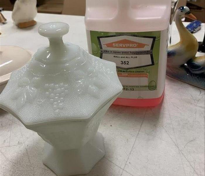 Bottle of cleaning solution that is red behind white urn sitting on countertop
