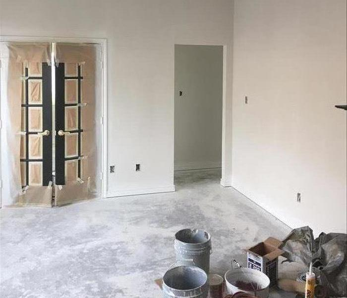 Room with covered doors and paint cans on the phone.