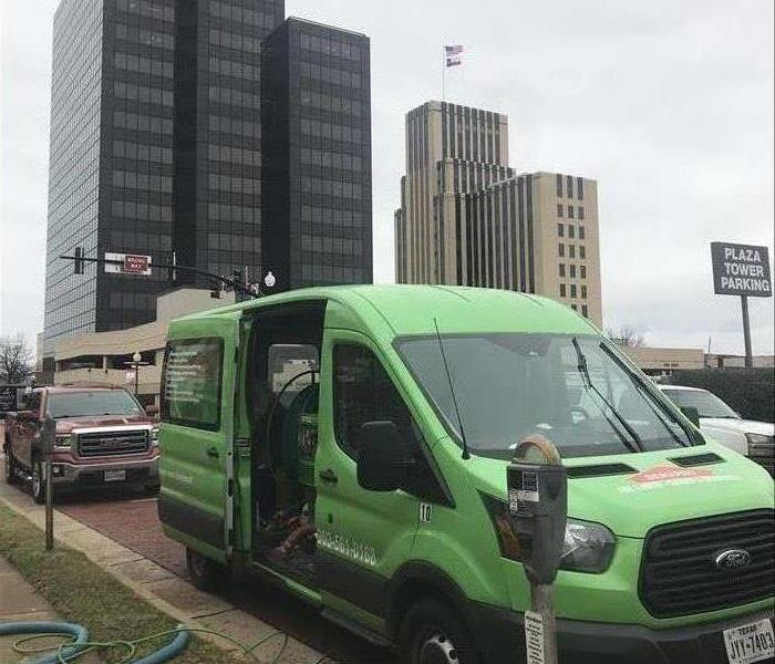 SERVPRO van outside of tall buildings.