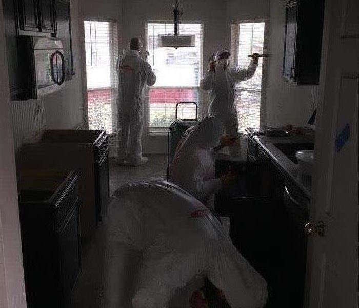 Four employees in PPE inside a home.