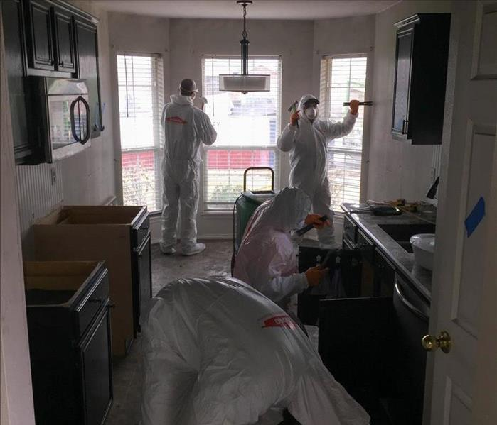 Four people in PPE cleaning.