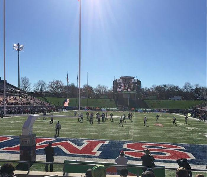 Green football field with players scattered across, Blue sky and sun shining